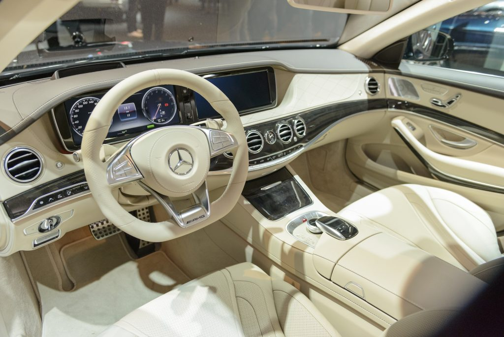 Dashboard on a Mercedes-Benz S500e Plug-in Hybrid luxury limousine sedan fitted with light leather seats, wood trim and a large information display on the dashboard.