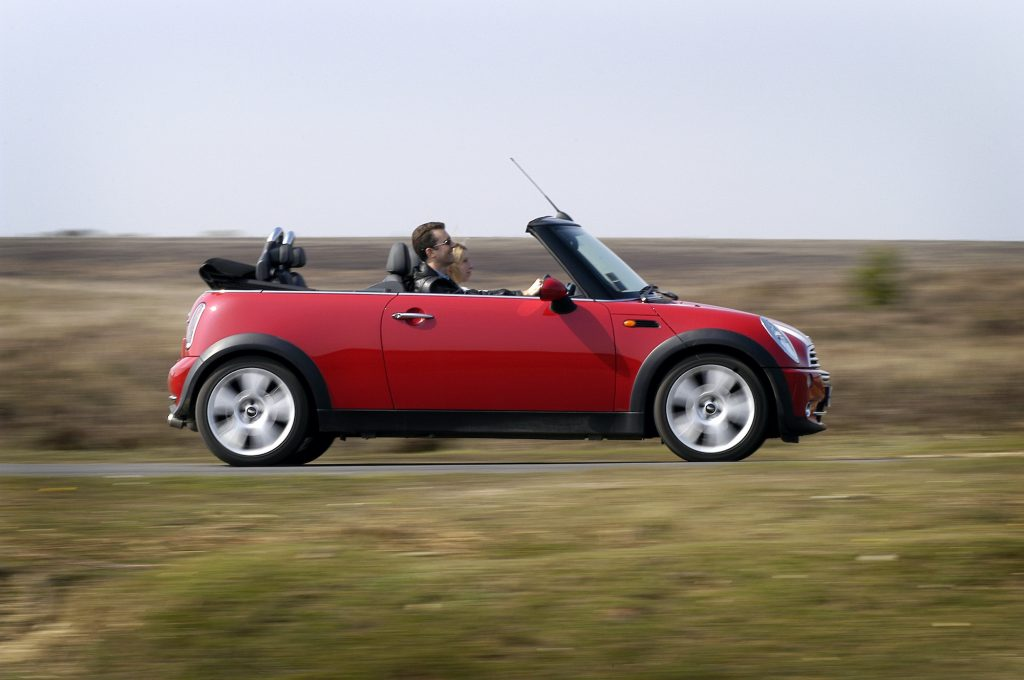 A Mini Cooper Convertible driving down the road