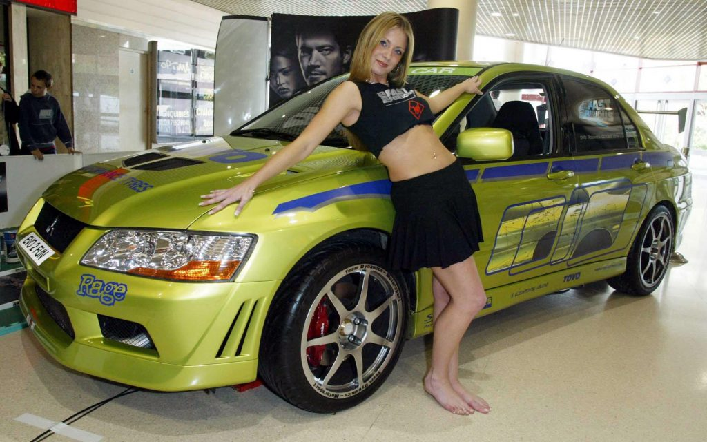 a model poses in front of the EVO from 2fast 2furious