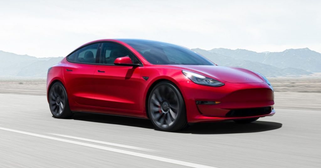 A red Tesla Model 3 drives down a highway.