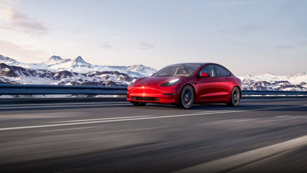 A red Tesla Model 3 driving on the highway.