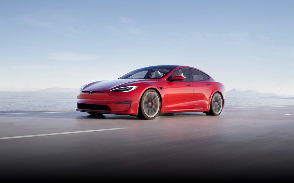 A red Tesla Model S Plaid driving down a highway.