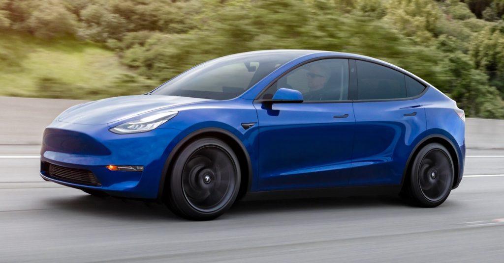 A blue Tesla Model Y drives down a road.