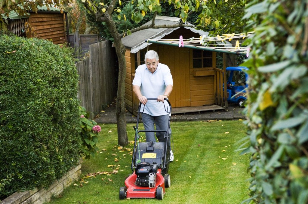 Pictured is an elderly man mowing his lawn