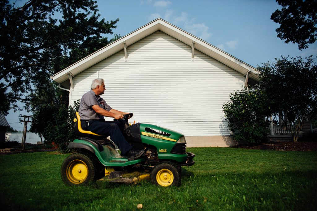 A man mowing a lawn on a riding lawn mower
