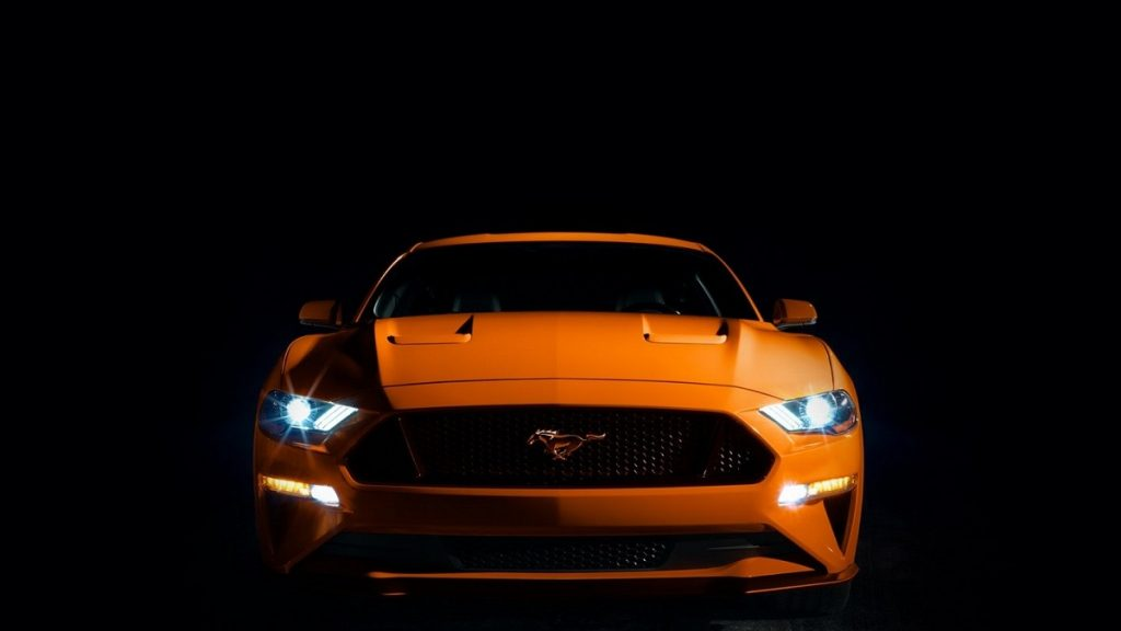 An orange 2021 Ford Mustang against a black background.