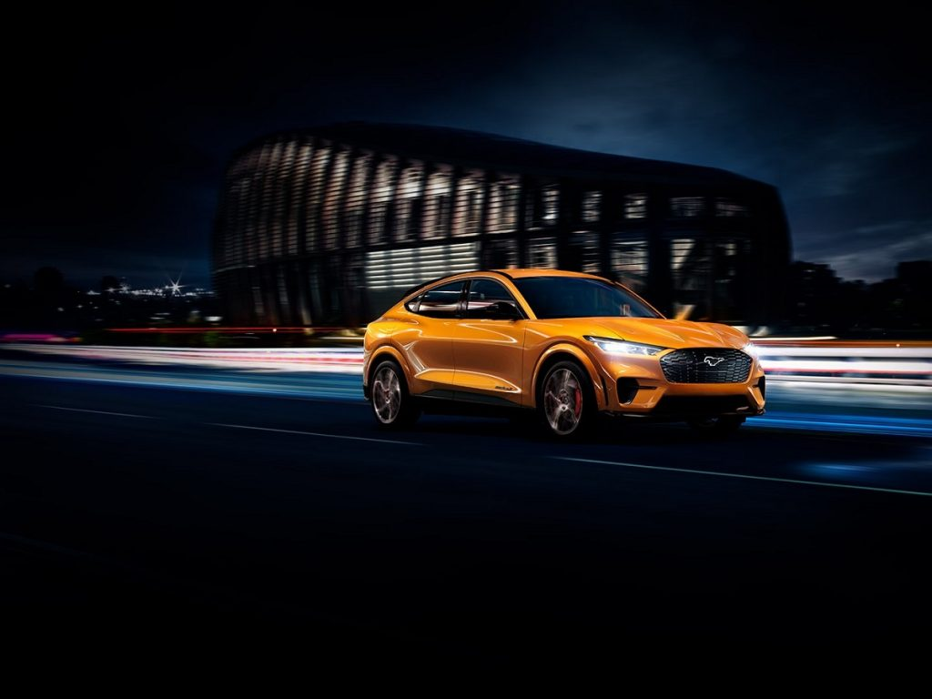 A yellow 2021 Ford Mustang Mach-E races through a city.