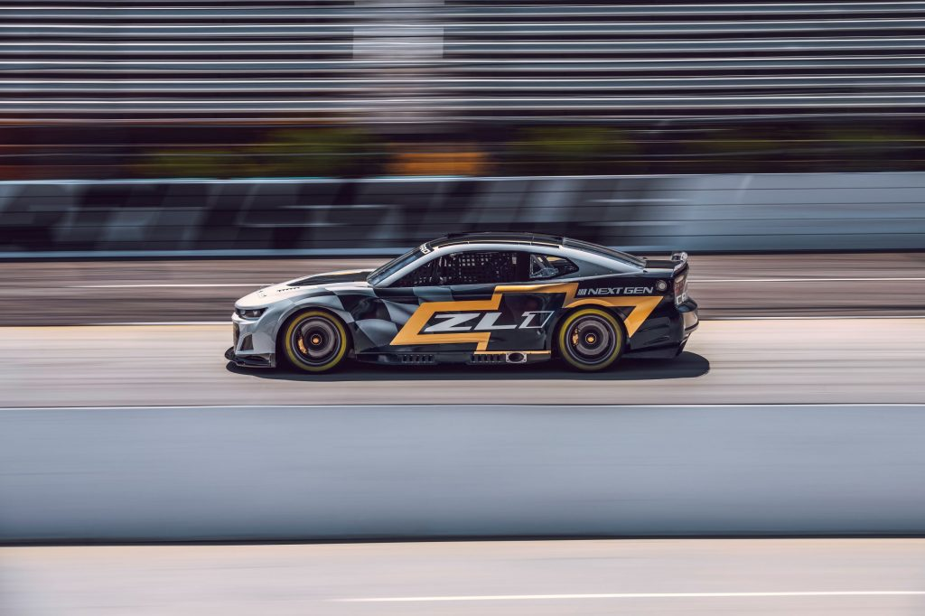 The side view of the silver-black-and-gold NASCAR Next Gen Chevrolet Camaro ZL1 speeding down a racetrack