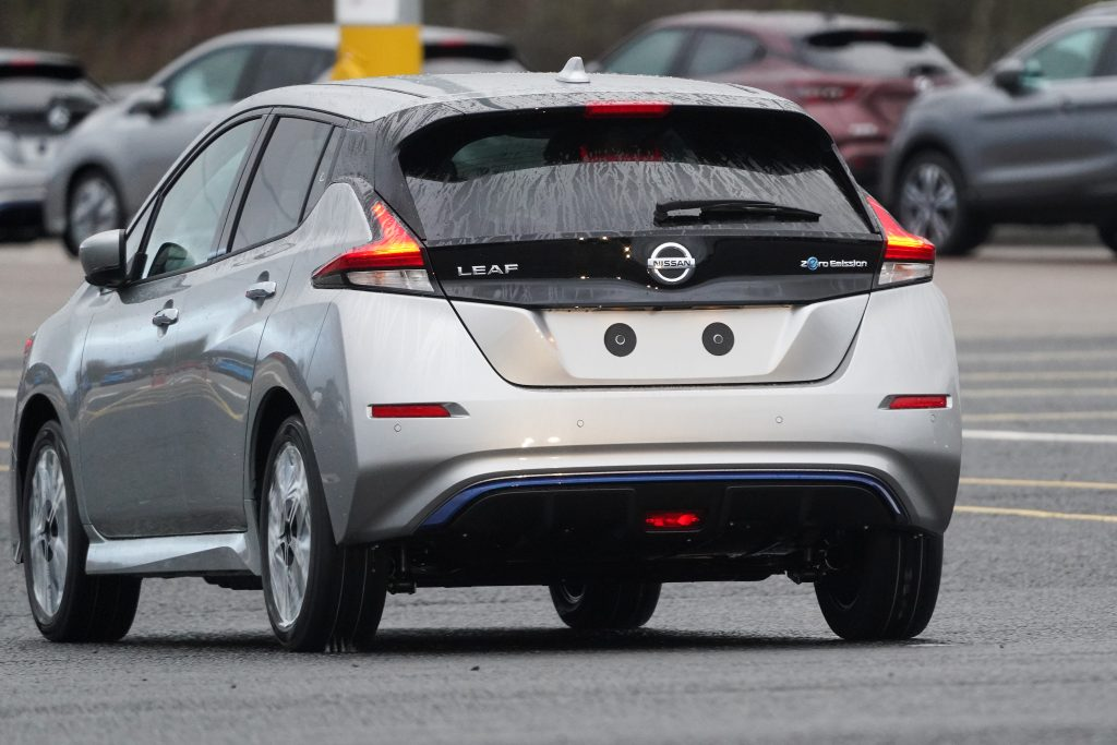 A newly manufactured gray Nissan Leaf electric vehicle is driven from the production line to be parked at the Nissan Motor Co. plant
