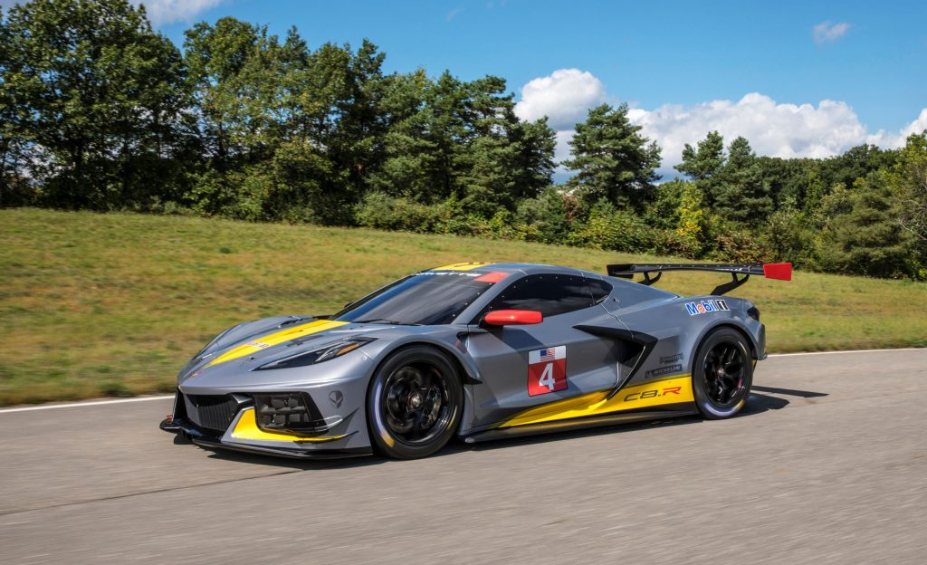 The gray-and-yellow No. 4 Chevrolet Corvette C8.R driving on a tree-line road
