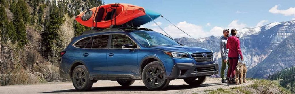 A blue 2021 Subaru Outback parked on a mountain with a couple and their dog standing nearby.