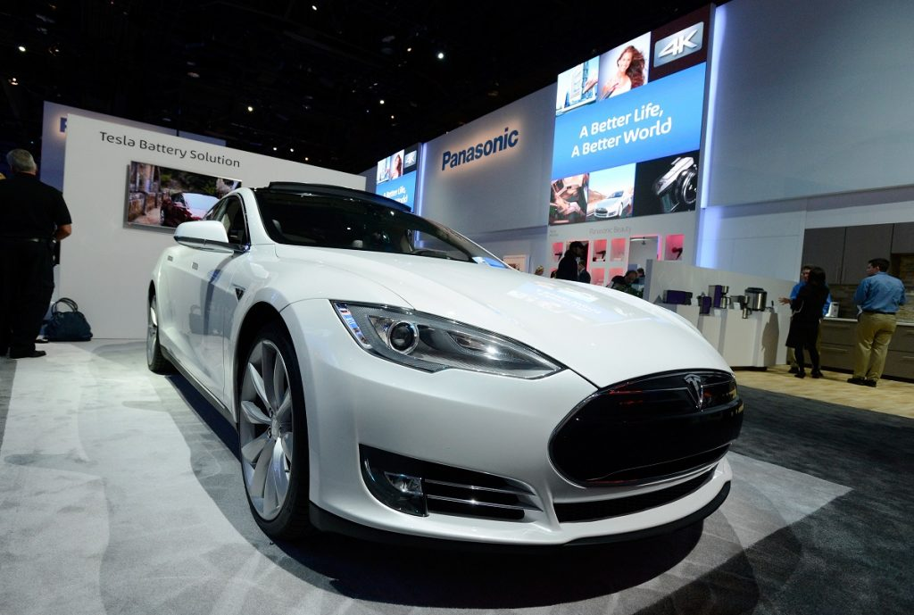 A white Tesla electric car on display at a Panasonic booth at a car show.