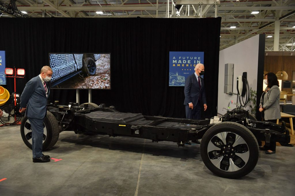 President Joe Biden examines the battery pack and chassis of a Ford EV