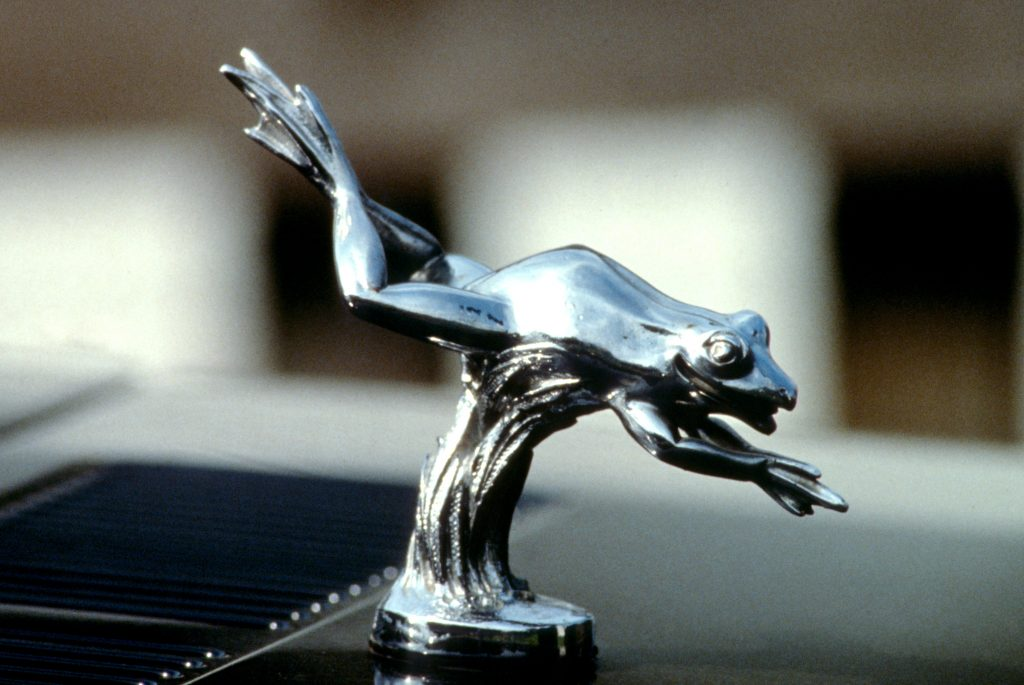 A silver hood ornament of a frog leaping forward as if diving into a pond