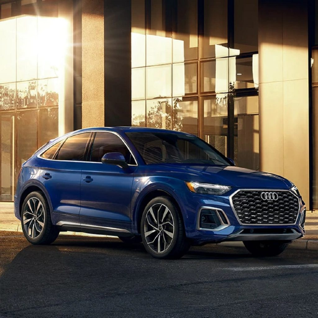 A blue 2021 Audi Q5 parked outside of a building.