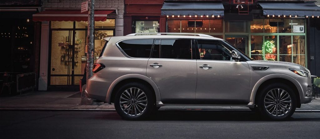 A gold 2021 Infiniti QX80 parked in front of a restaurant.