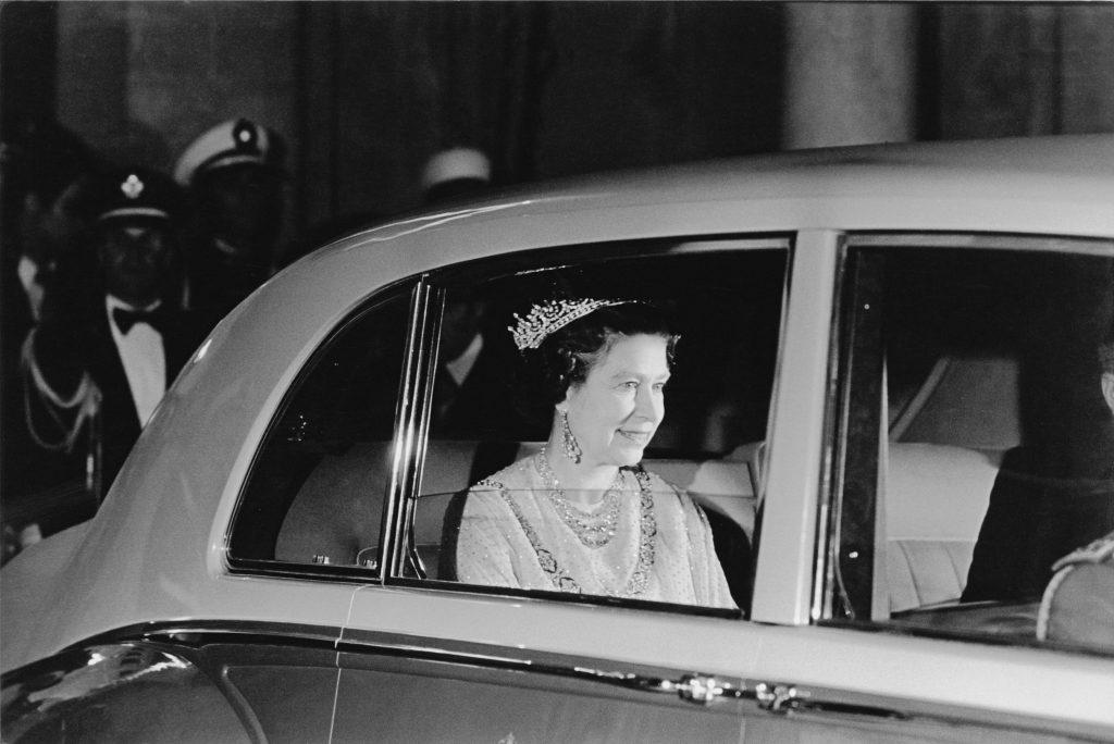 Queen Elizabeth II in the rear seat of a car