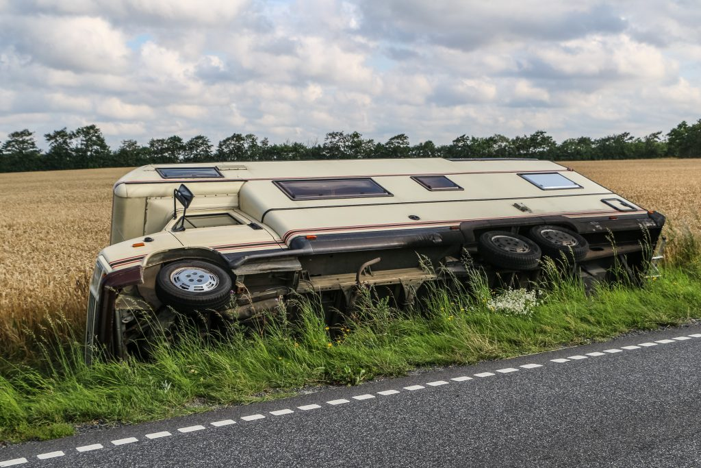 A recreational vehicle on its side in a ditch