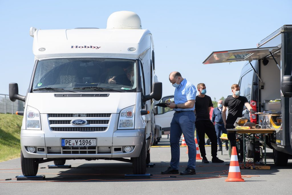 Saxony, Laatzen: Matthias Krebs (r), member of the Traffic, Technology and Environment Team at ADAC Lower Saxony / Saxony-Anhalt, talks to a motorhome driver after weighing the vehicle's weight