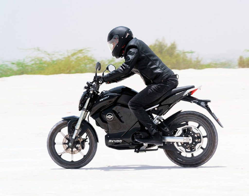 A man clad in all black on a black electric motorcycle.