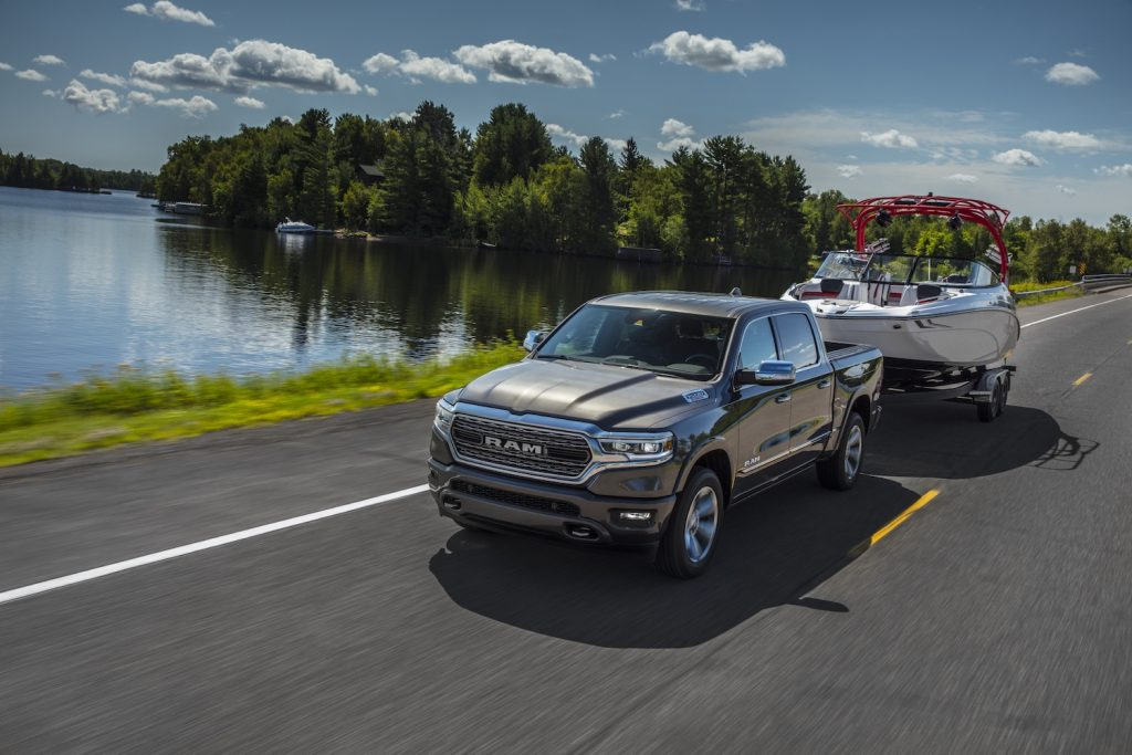 A 2021 Ram 1500 towing a boat by a lake