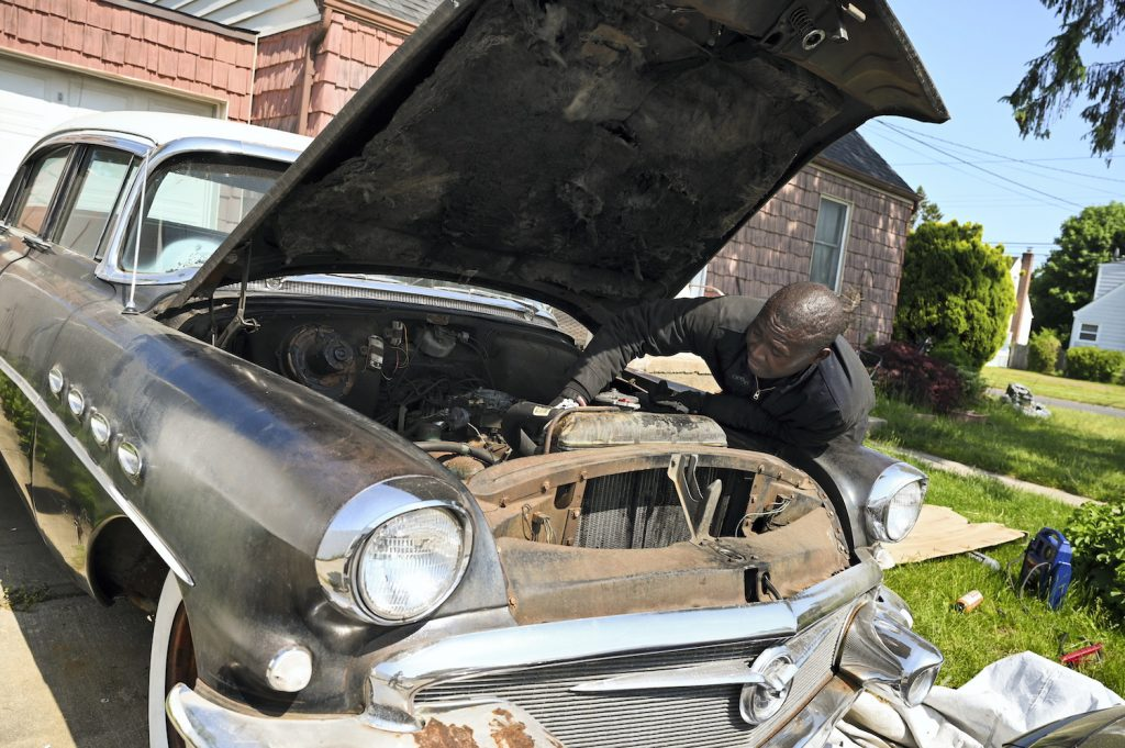 Long Island man works on engine of classic car 1956 Buick