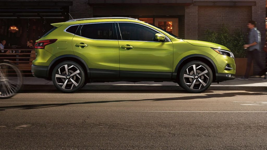 A green 2021 Nissan Rogue Sport is parked on a city curb.