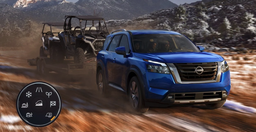 A blue 2022 Nissan Pathfinder towing an ATV with drive modes shown