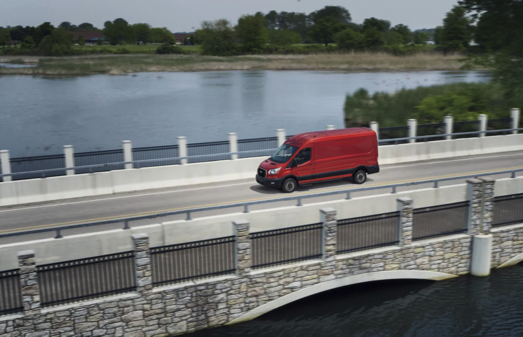 A red 2021 Ford Transit van driving over a bridge