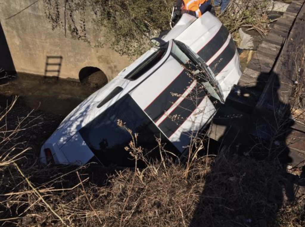 An image of a crashed Ford Mustang outdoors.