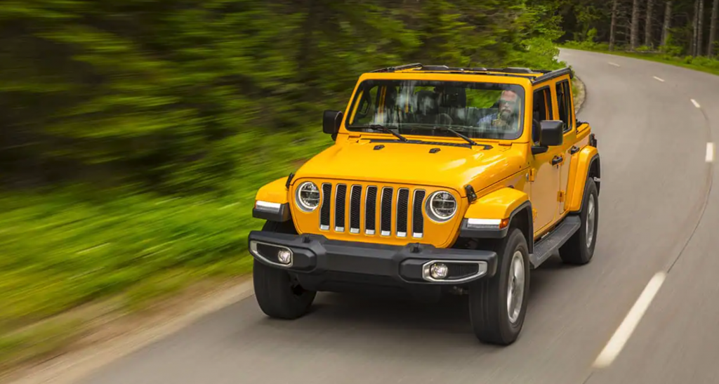 A yellow 2021 Jeep Wrangler driving down a forrest road