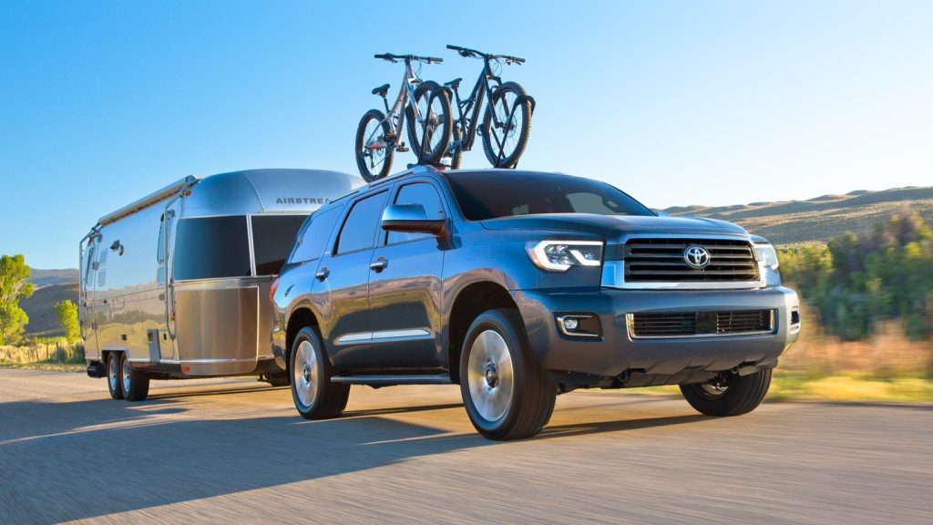 A blue 2021 Toyota Sequoia with a trailer driving up a mountain.