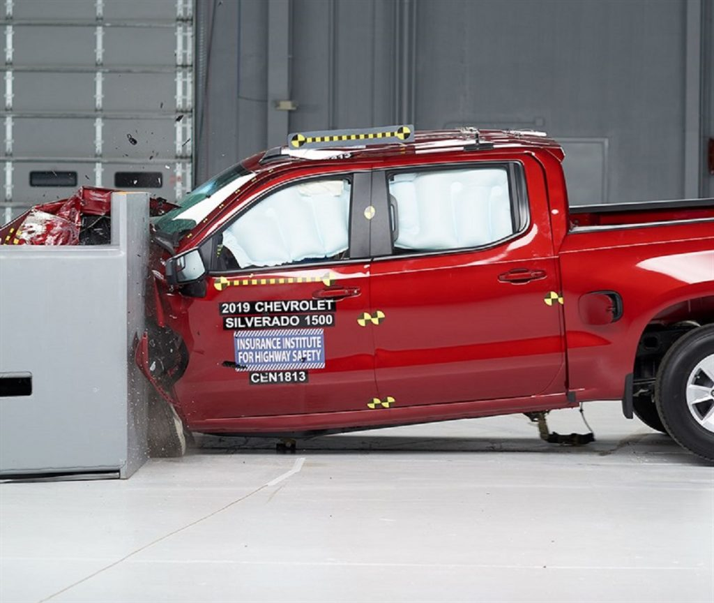 A red Chevy Silverado 1500 is smashed into a wall inside the IIHS laboratories.
