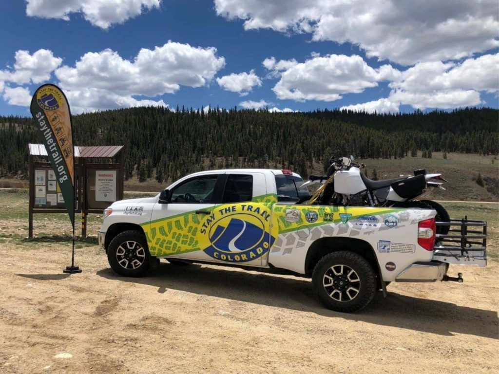 The Stay the Trail truck and dirt bike parked in the dirt to help ATV and dirt bikers learn the OHV rules