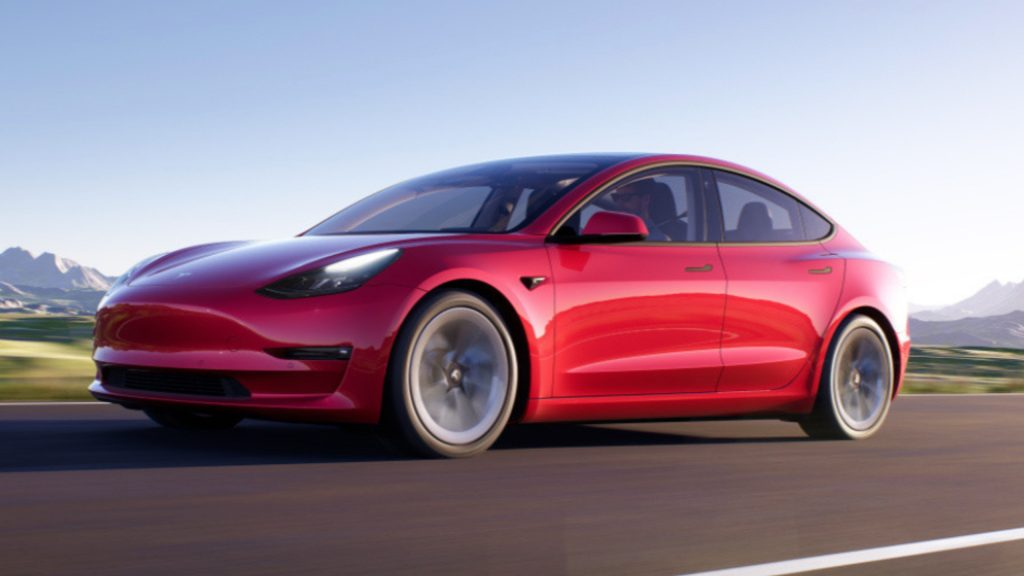 An image of a red Tesla Model 3 out on the road.