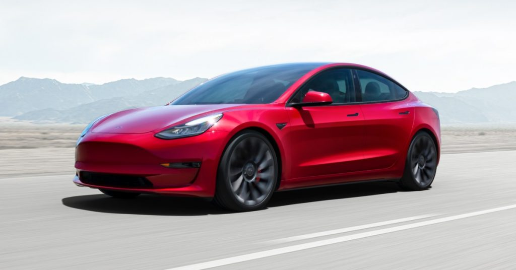 A red Tesla Model 3 drives down the highway.