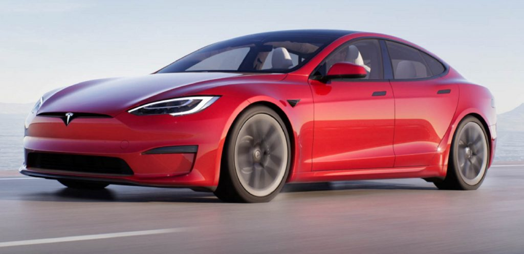 A red Tesla Model S Plaid drives down a road