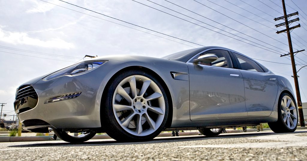 The Tesla Motors Inc. Model S electric car sits under power lines after being unveiled at the Space Exploration Technologies (SpaceX) factory.