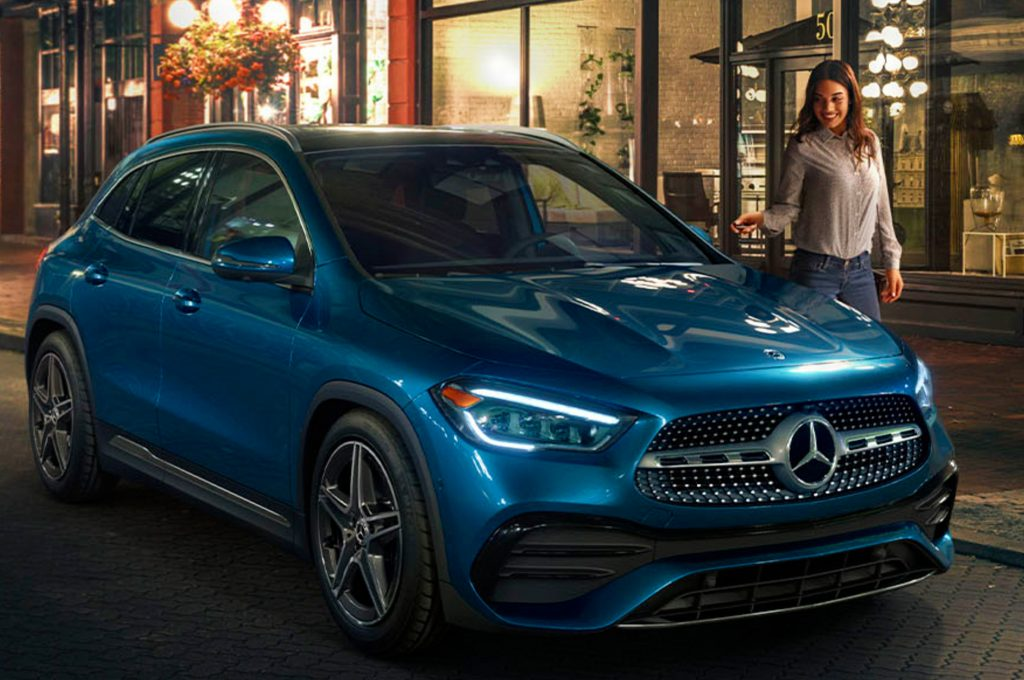 a light blue 2021 mercedes-benz GLA-Class on the curb of a fashionable night time cityscape