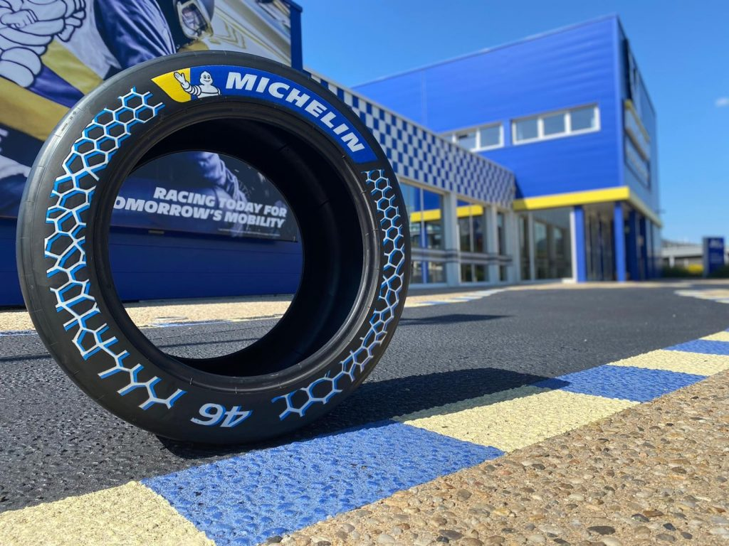 The Michelin racing tire with 46% sustainable materials unveiled at the 2021 Movin'On Summit on a racetrack by a blue-and-yellow Michelin building