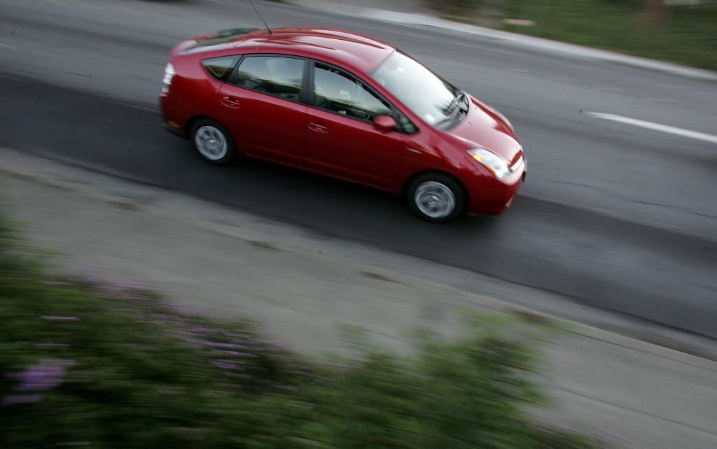 A Toyota Prius hybrid vehicle is seen driving down the street