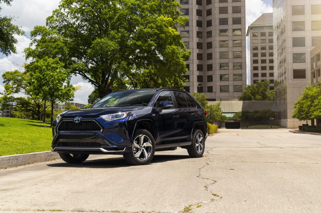 A dark blue Toyota RAV4 prime shot at front 3/4 view with buildings in the background.