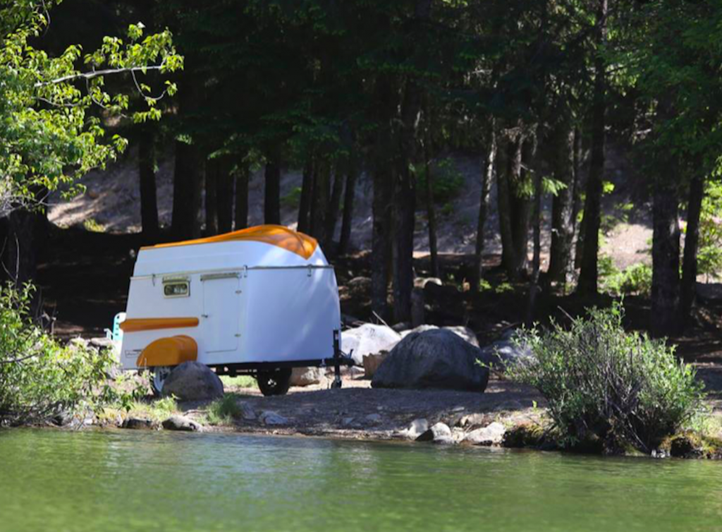 an orange and white boat trailer parked by the shore in a wooded area