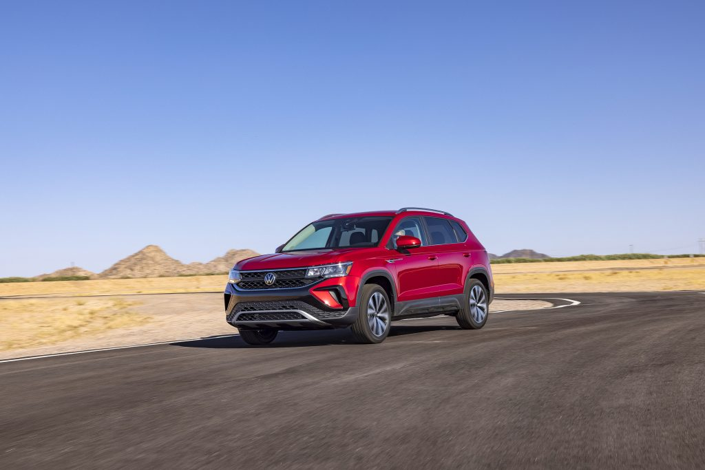 The red 2022 Volkswagen Taos driving along a desert road