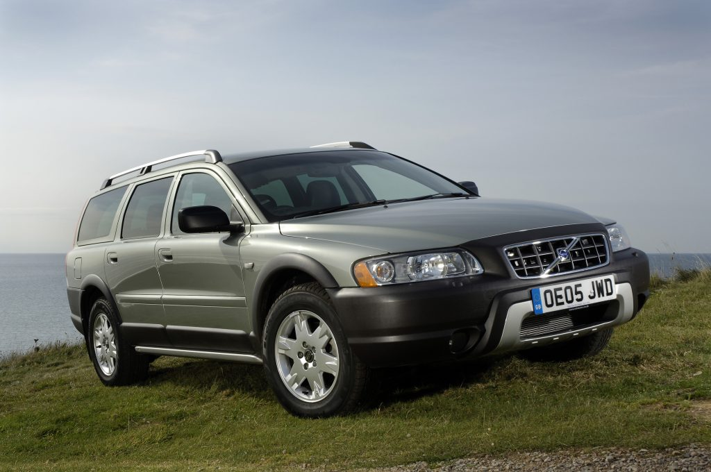 A silver Volvo XC70 SUV parked on a hill overlooking water