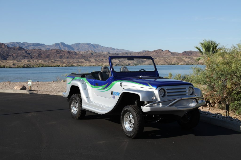 A silver-green-and-blue WaterCar Panther on a road by a lake