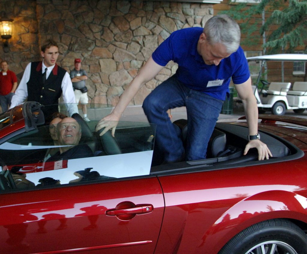 Anderson Cooper jumps out of the back of a red convertible Mustang.