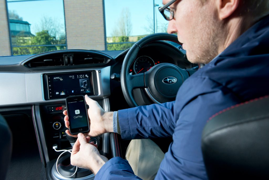 Portrait of a driver with an Apple iPhone 5 and Pioneer head unit fitted in a Subaru BRZ.