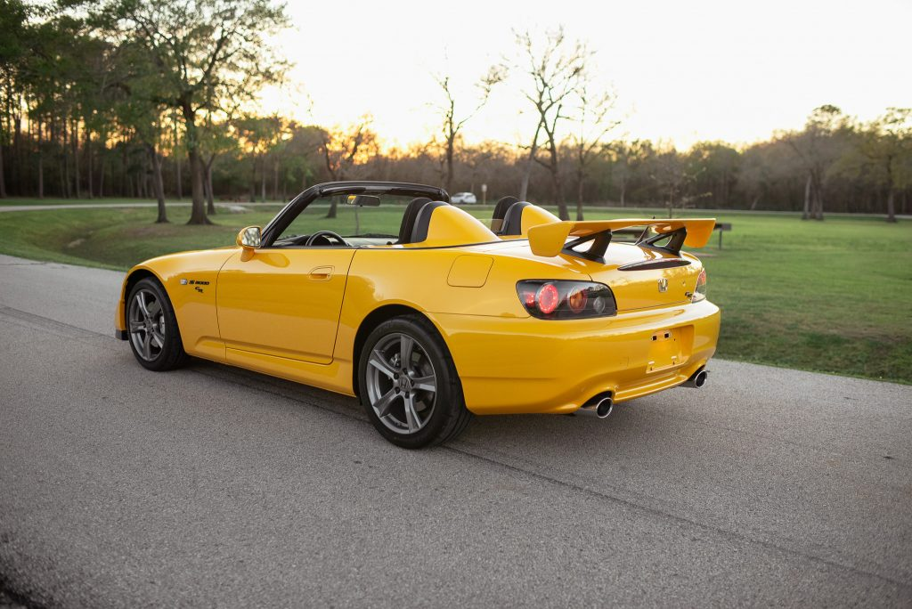 A yellow open-roof Honda S2000