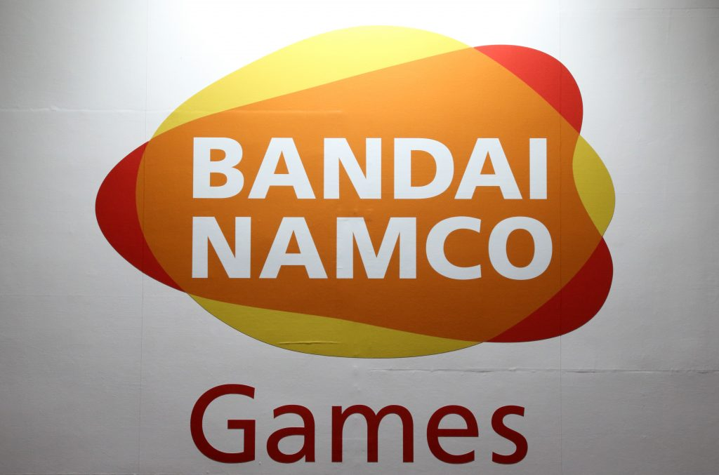 the Bandai Namco logo on a background of red, yellow, and orange